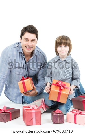 Father and son with a gift box looking at camera isolated. Holiday concept.