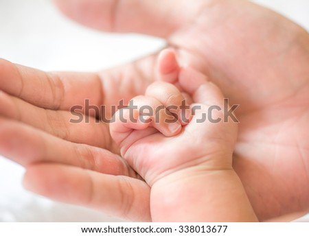 father holding baby hand