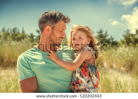 father holding daughter in the arms
