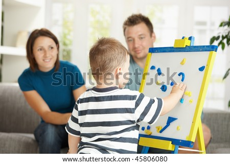 Father, mother and boy child playing together with toy whiteboard, learning letters and numbers.