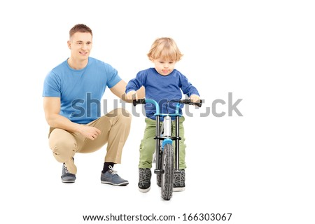 Father near his son trying to riding a bicycle isolated on white background