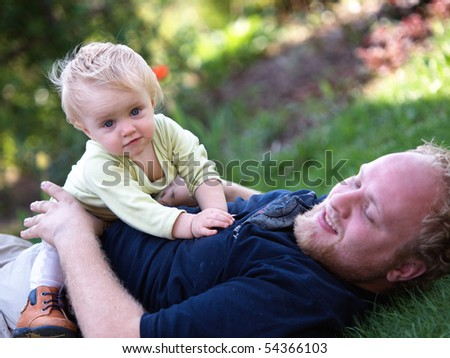 Father playing with child on a lawn