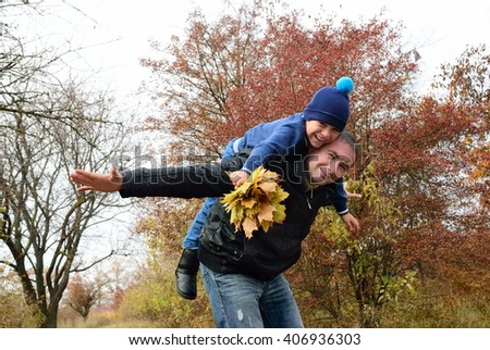 Father playing with his son in the autumn forest