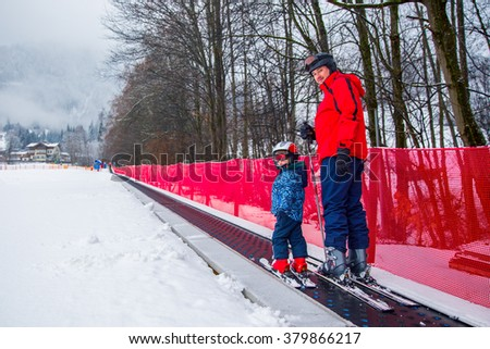 Father teaching skiing his happy little son during a winter vacation in Alpine ski resort in Austria. Little kid having fun and going up to the slope on the magic carpet lift.