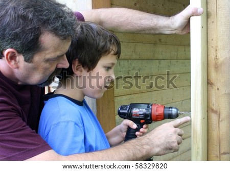 father teaching son to use a drill