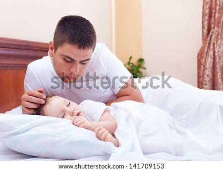 father watching the son sleeps, home indoors