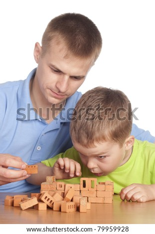 father with his son playing at table