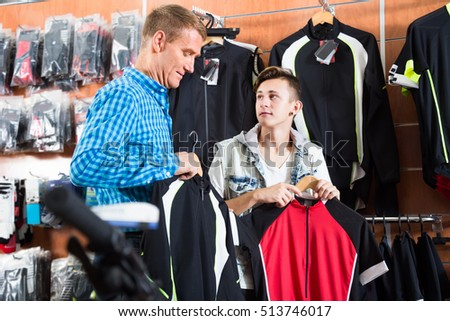 father with teenager son buying special clothes for bicycling in sport shop