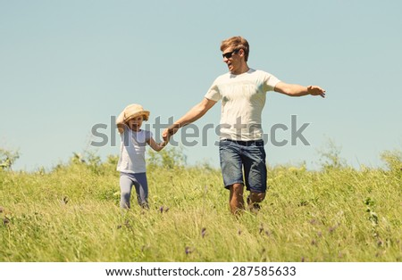 Father with the daughter running on the field
