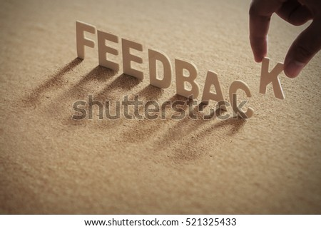 FEEDBACK wood word on compressed board,cork board with human's finger at K letter