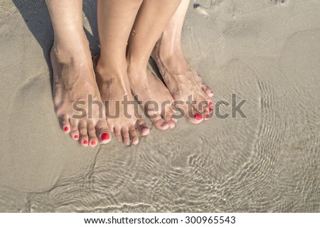 feet of child and mom in the sea sand, from above