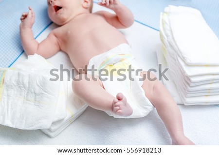 Feet of newborn baby on changing table with diapers. Cute little girl or boy two weeks old. Dry and healthy body and skin concept. Baby nursery