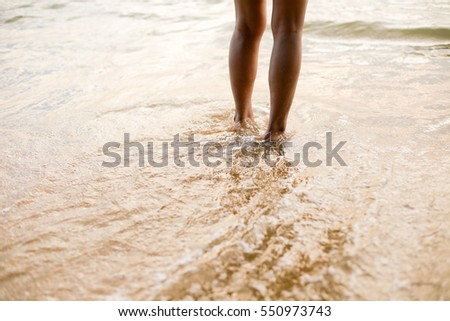 Feet of the person standing in the water