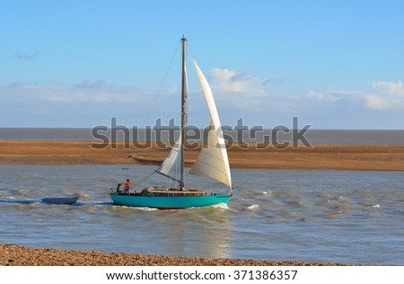 FELIXSTOWE, SUFFOLK, ENGLAND - NOVEMBER 10, 2013: Yacht leaving Felixstowe Ferry at the mouth of the river Deben.
