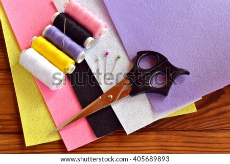 Felt sheets, scissors, thread, needle, pins on a brown wooden background