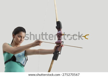 Female archer aiming bow and arrow against gray background