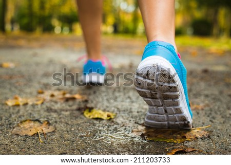 Female athlete ready for autumn running challenge in park wet track. Runner footwear on training.