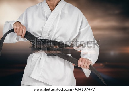 Female athlete tightening her judo belt against view of sport ground outdoor