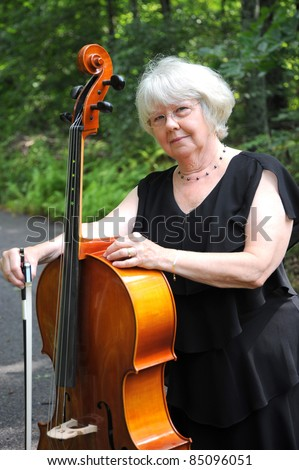 Female cellist music teacher standing outside with her cello.