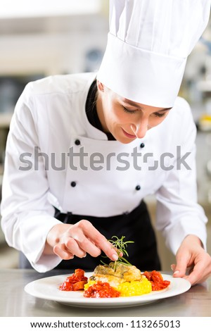 Female Chef in hotel or restaurant kitchen cooking, she is finishing a dish on plate