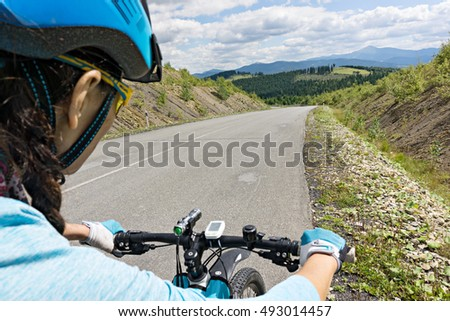 Female cyclist riding her bike on a road. View from the back.