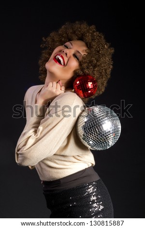 Female disco dance party girl holding two shiny disco balls on black background