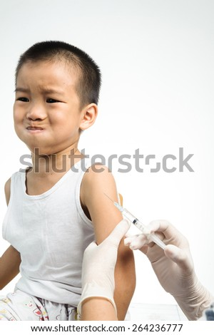 Female doctor doing injection to little boy that looks fear