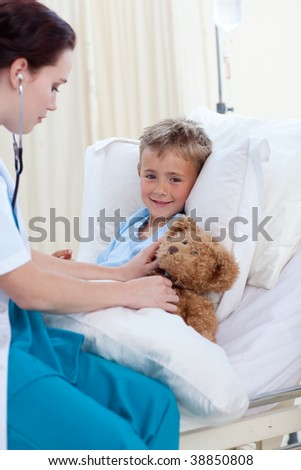 Female doctor listening to a child chest and a teddy bear with stethoscope in bed