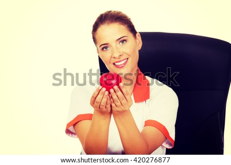 Female doctor  sitting behind the desk and holding heart toy
