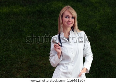 Female doctor smiling on the background of the grass.