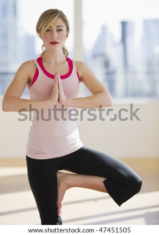 female doing balanced yoga position alone in gym