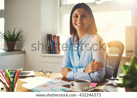 Female entrepreneur sitting at her desk in a office smiling at the camera with arms crossed