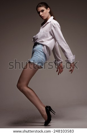 Female fashion model  stay bending the knees in white man shirt