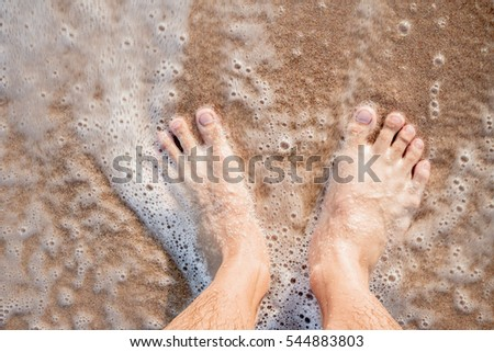 Female feet relaxing on the beach