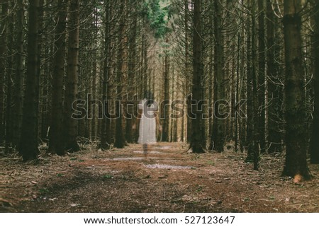 Female ghost walking barefoot through the forest in white dress