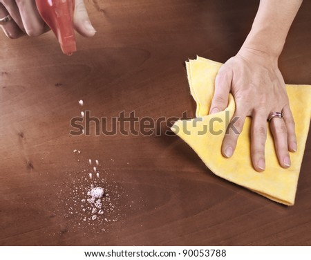 Female hand cleaning dining table