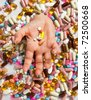 Female hand drowning in an ocean of medical pills - stock photo