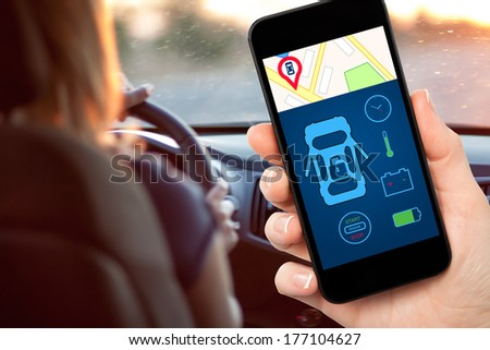 female hand holding a phone with interface auto alarm on a screen on a background woman driving a car