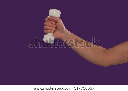 Female hand holding a white dumbbell with the arm slightly flexed over a purple studio background