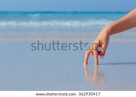 Female hand playing in the water on the white sand beach on blue sea background