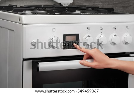 Female hand turning on white kitchen gas stove on gray background