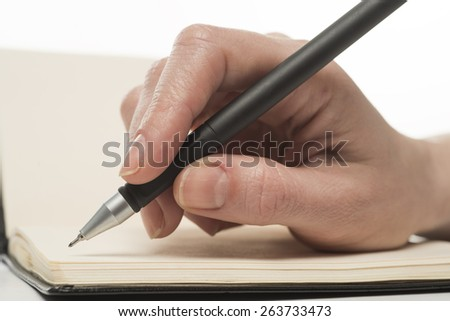 Female hand writing in notebook, isolated on white
