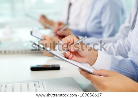 Female hands holding pen and clipboard while making notes with business partners working on background