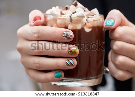 Female hands with bright festive manicure design holding glass mug with hot cocoa and marshmallows. Winter holidays. Christmas and New Year.