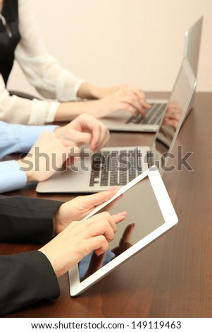 Female hands with digital tablet on office background.