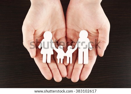 Female hands with family model on dark wooden background