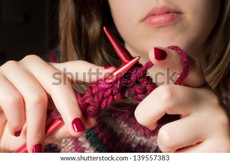 Female hands with knitting needles while knitting