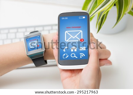 Female hands with smartwatch and phone with email or sms on the screen.