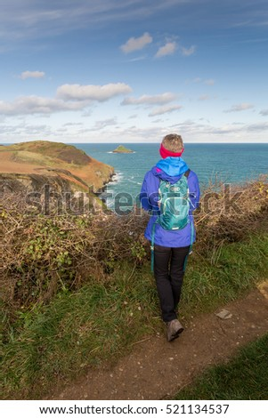 female hiker rambler looking out to sea in cornwall england uk near the rumps