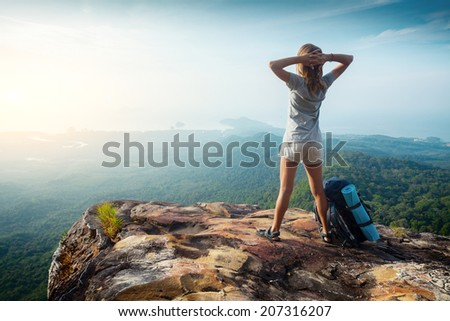 Female hiker relaxing on top of the hill